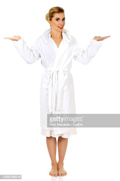 full length portrait of young woman wearing bathrobe standing on white background - bathrobe stock pictures, royalty-free photos & images