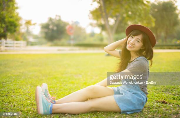Full Length Portrait Of Young Woman Wearing Hat While Sitting On Field At Park