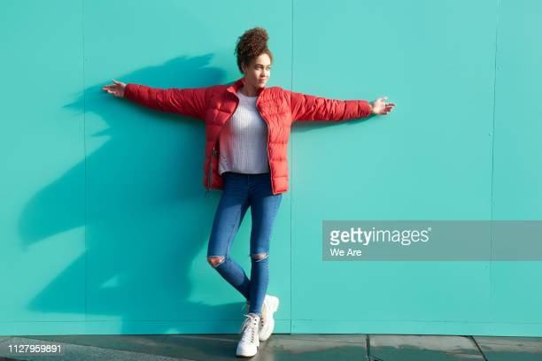 full length portrait of young woman with arms outstretched. - padded jacket stock pictures, royalty-free photos & images