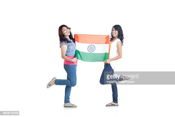 full length portrait of young women in casuals holding indian flag over white background - indian flag stock pictures, royalty-free photos & images