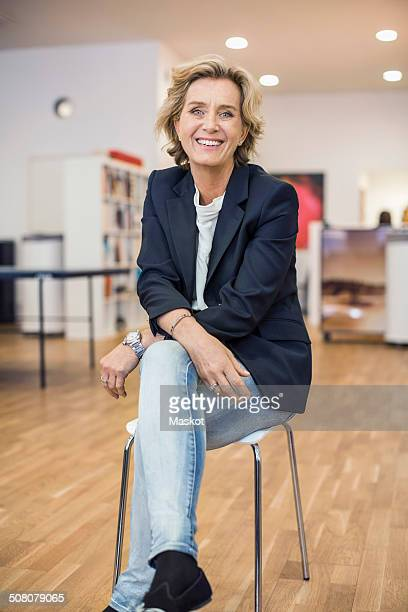 Full length portrait smiling businesswoman sitting on chair in office