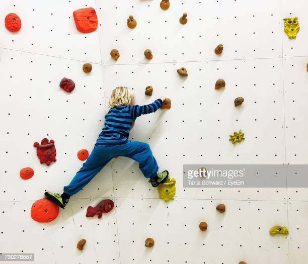 full length rear view of boy climbing wall - free climbing stock pictures, royalty-free photos & images