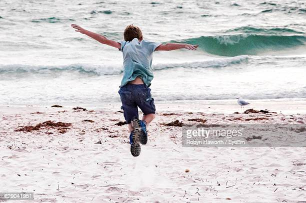 Full Length Rear View Of Boy Jumping On Shore