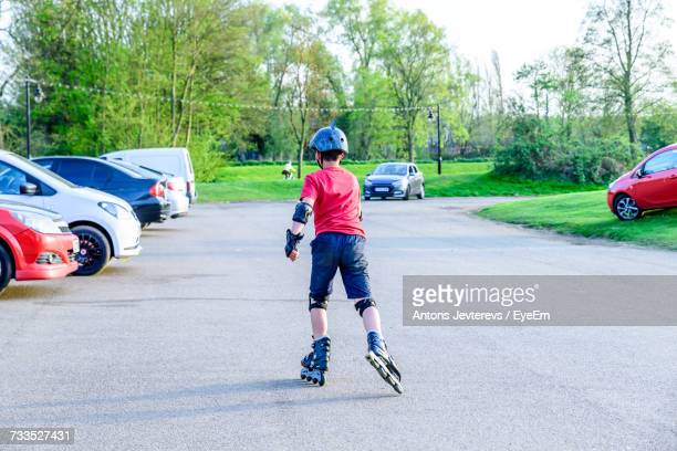 Full Length Rear View Of Boy Roller Skating On Road In Park