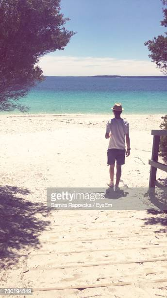 Full Length Rear View Of Boy Standing At Beach On Sunny Day