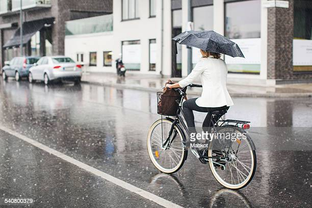 Full length rear view of businesswoman riding bicycle on wet city street during rainy season
