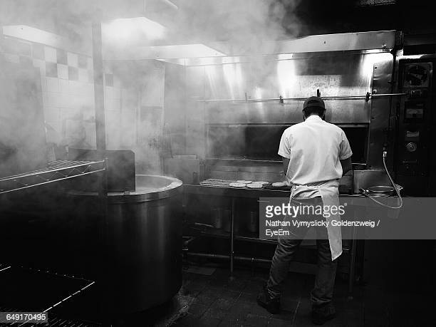 Full Length Rear View Of Chef Working In Commercial Kitchen