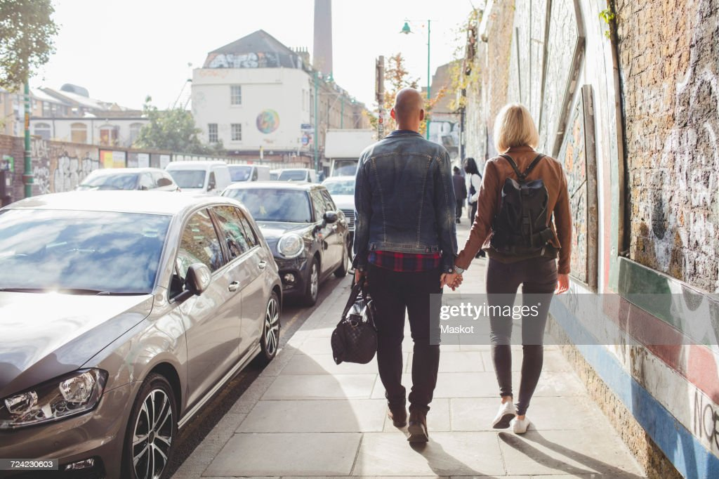 Full length rear view of couple holding hands while walking on sidewalk by traffic in city : Stock Photo