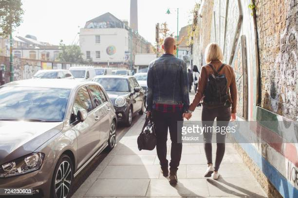 Full length rear view of couple holding hands while walking on sidewalk by traffic in city