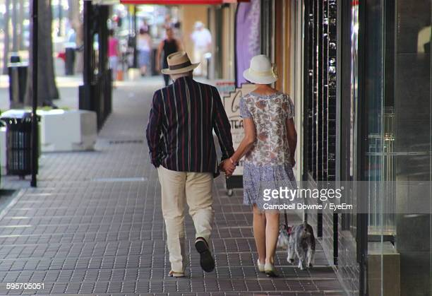 full length rear view of couple walking with dog on sidewalk in city - campbell downie stock pictures, royalty-free photos & images