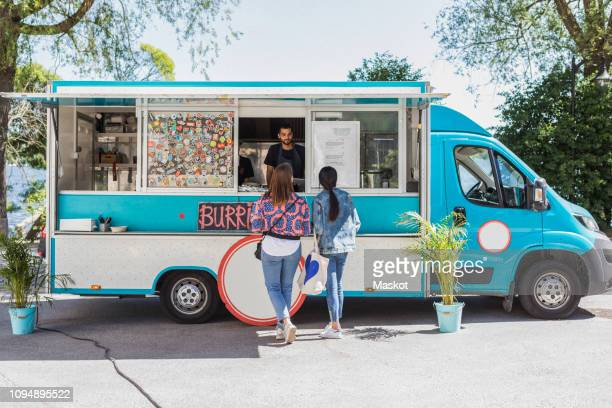 full length rear view of female friends talking with male food truck owner in city on sunny day - food truck fotografías e imágenes de stock