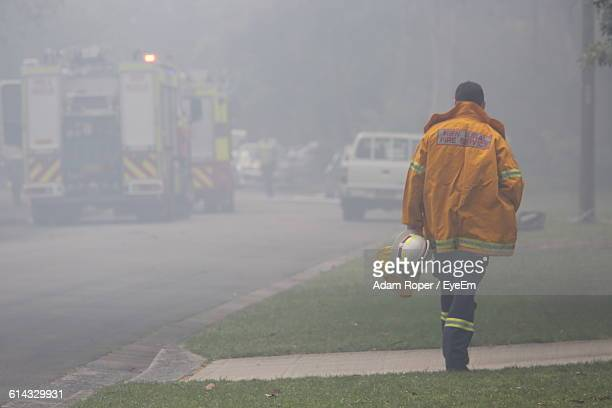 full length rear view of firefighter walking on sidewalk - firefighter stock pictures, royalty-free photos & images