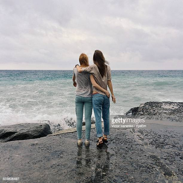 Full Length Rear View Of Friends Standing On Rock Viewing Sea
