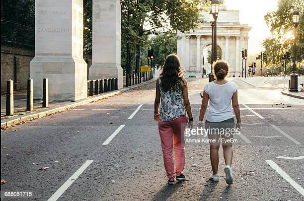 Full Length Rear View Of Friends Walking On Street By Wellington Arch At Morning