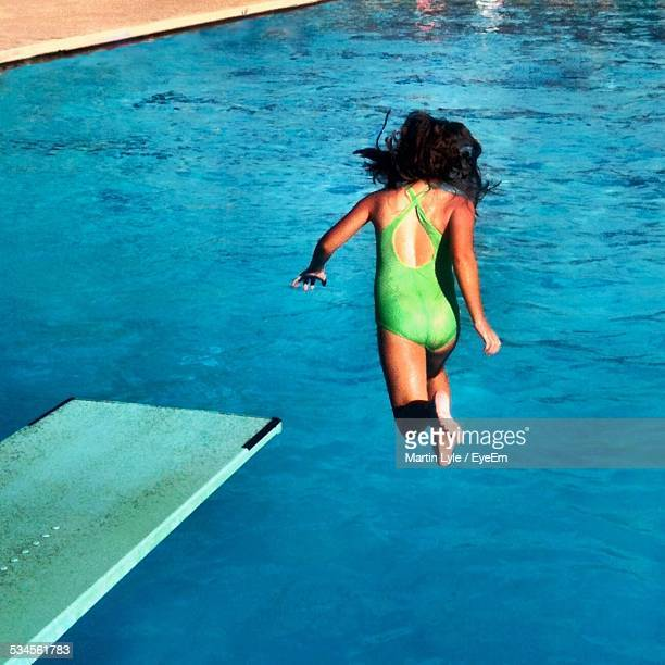 Full Length Rear View Of Girl Jumping In Swimming Pool
