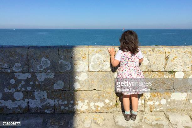 Full Length Rear View Of Girl Standing By Retaining Wall Against Sea