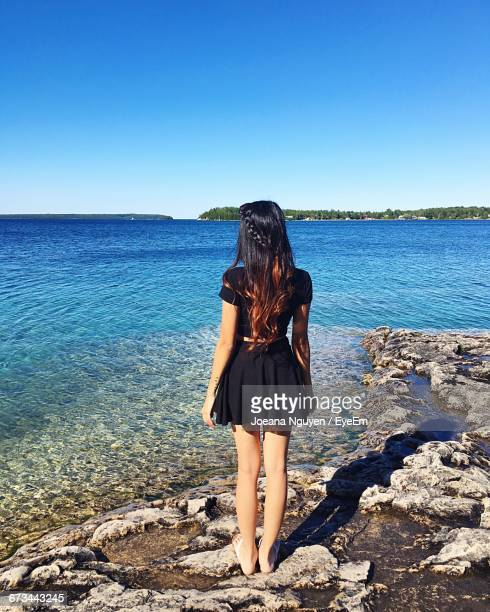 Full Length Rear View Of Girl Standing In Black Dress At Beach Against Clear Blue Sky On Sunny Day