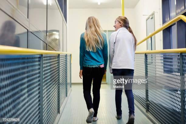 Full length rear view of girls walking in school corridor