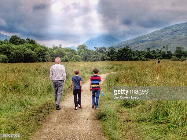 Full Length Rear View Of Grandfather Walking With Grandchildren On Grassy Field Against Cloudy Sky