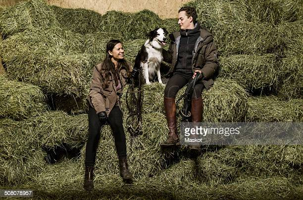 Full length rear view of happy young couple with dog sitting on hay stack in stable