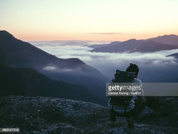 full length rear view of hiker crouching on cliff by cloudscape and mountains at morning - rucksacktourist stock-fotos und bilder