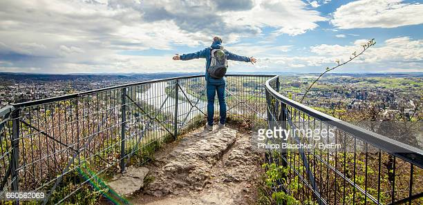 Full Length Rear View Of Hiker Standing At Observation Point With Arms Outstretched Against Sky