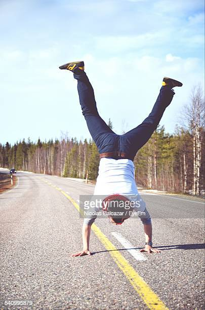 Full Length Rear View Of Man Doing Handstand On Country Road Against Cloudy Sky