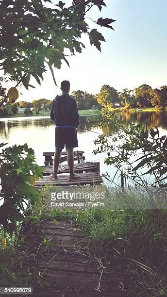 full length rear view of man fishing on pier in front of lake - carvajal stock photos and pictures