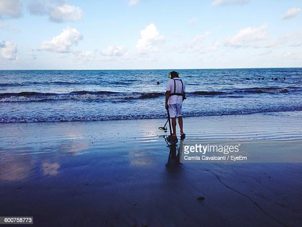 Full Length Rear View Of Man Holding Metal Detector On Beach