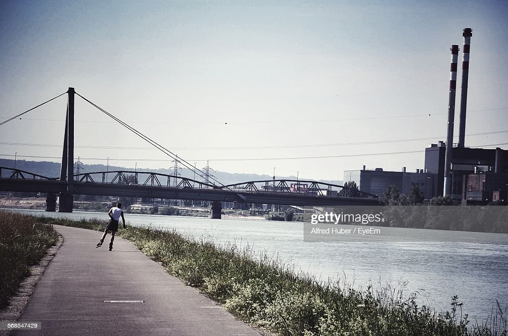 Full Length Rear View Of Man Inline Skating On Road By River : Stock Photo