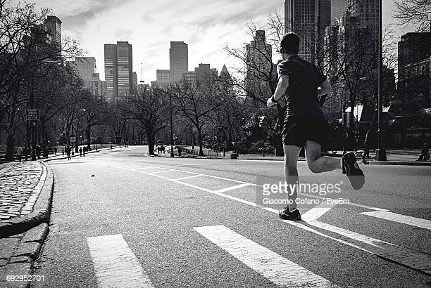 Full Length Rear View Of Man Jogging On Street In City