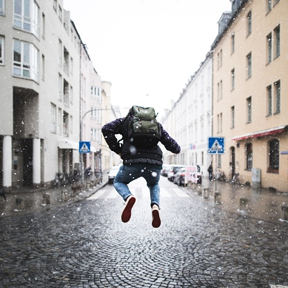 Full Length Rear View Of Man Jumping On Street In City Against Sky - gettyimageskorea
