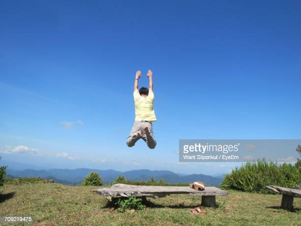 Full Length Rear View Of Man Jumping Over Bench At Cliff Against Blue Sky