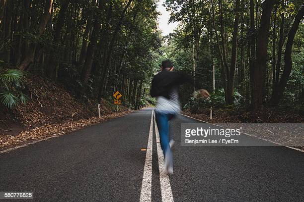 Full Length Rear View Of Man Running On Road In Forest