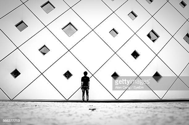 Full Length Rear View Of Man Standing Against Pattern Wall