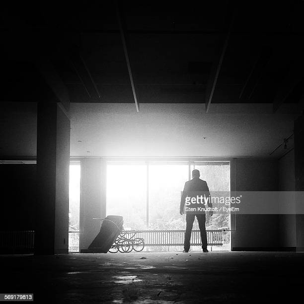 Full Length Rear View Of Man Standing In Abandoned Room