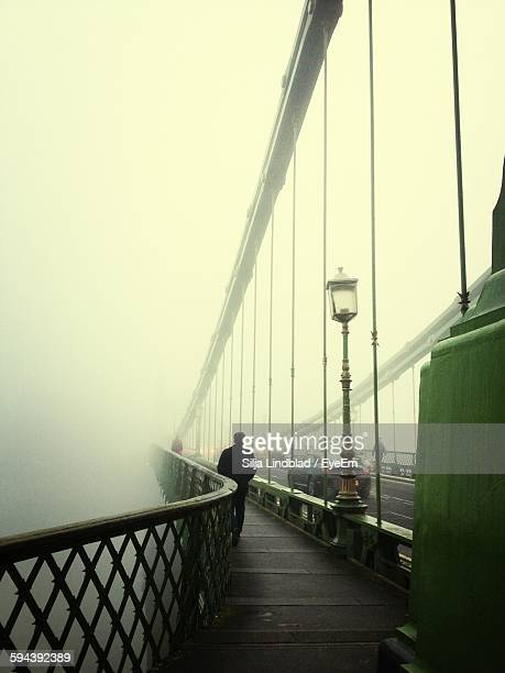 Full Length Rear View Of Man Standing On Bridge During Foggy Weather