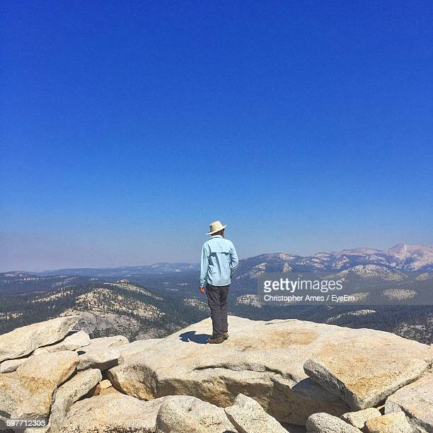 Full Length Rear View Of Man Standing On Cliff Against Clear Blue Sky