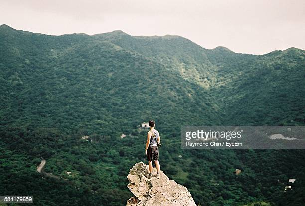 Full Length Rear View Of Man Standing On Cliff Against Mountains