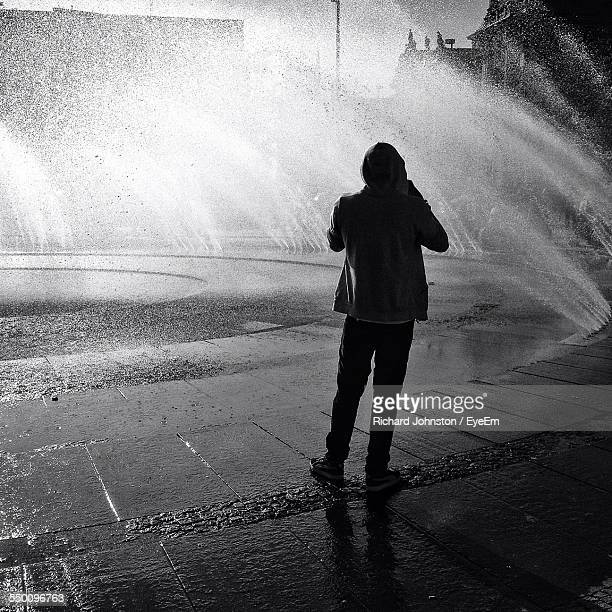 Full Length Rear View Of Man Standing Under Water Fountain