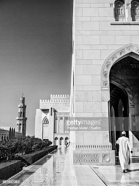 Full Length Rear View Of Man Visiting Mosque Against Clear Sky