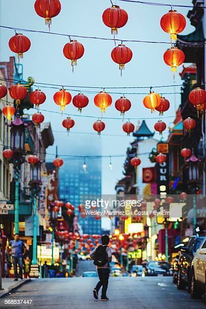 Full Length Rear View Of Man Walking In City Street Above Chinese Lanterns At Dusk