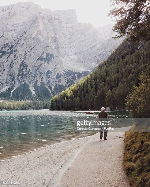 Full Length Rear View Of Man Walking On Lakeshore Against Mountains