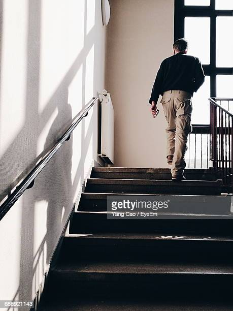 full length rear view of man walking on stairs at home - vertikal stock-fotos und bilder