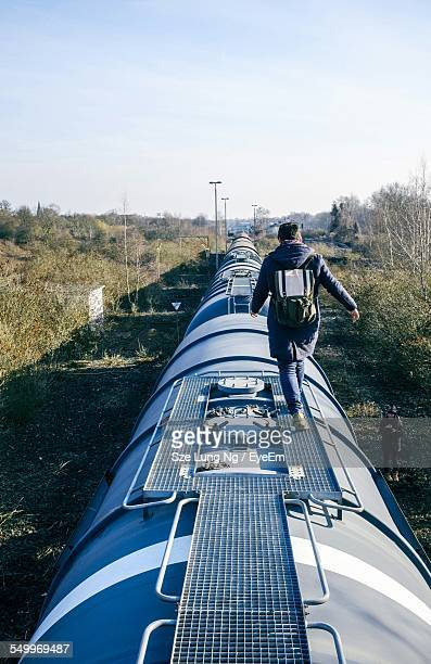 full length rear view of man walking on top of train against sky - oben stock-fotos und bilder