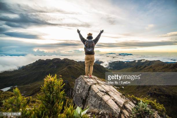 full length rear view of man with arms raised standing on rock at mountain against sky - un solo hombre fotografías e imágenes de stock