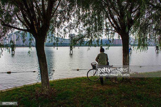 full length rear view of man with bicycle on riverbank - parham emrouz stock pictures, royalty-free photos & images