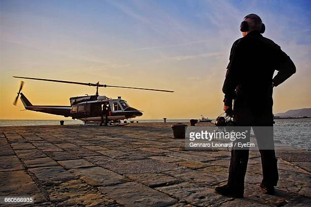 full length rear view of military worker standing by helicopter at port during sunset - helicopter rotors stock photos and pictures