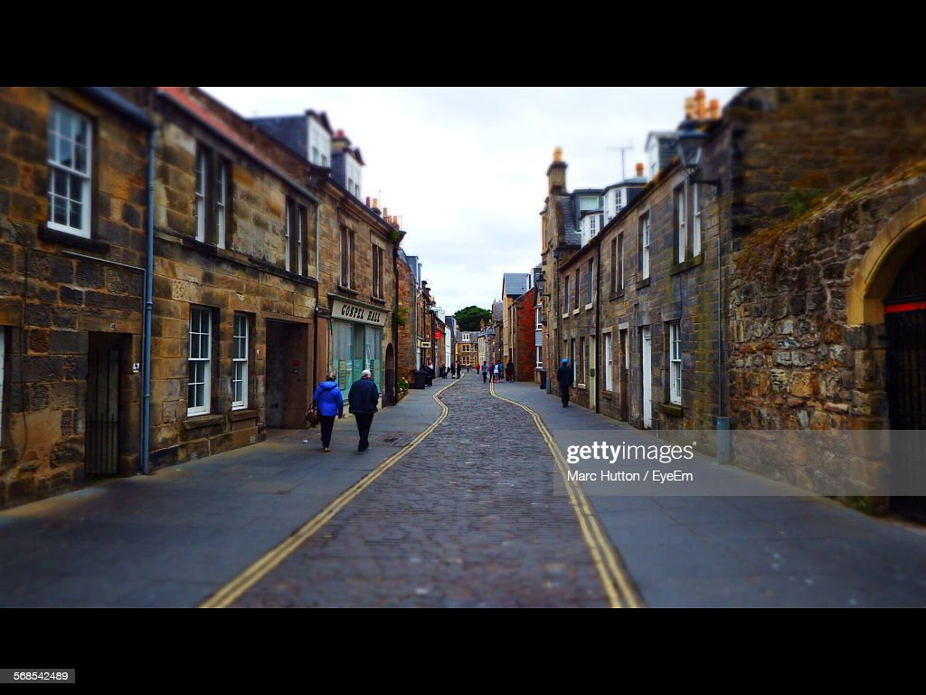Full Length Rear View Of People Walking On Street In Town Against Sky : Stock Photo