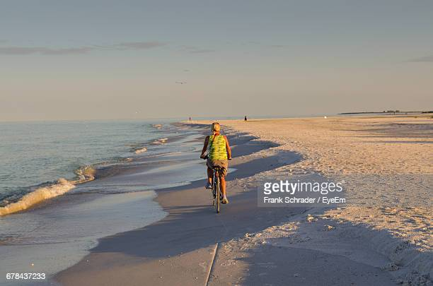 full length rear view of person riding bicycle at beach against sky on sunny day - anna maria island stock pictures, royalty-free photos & images